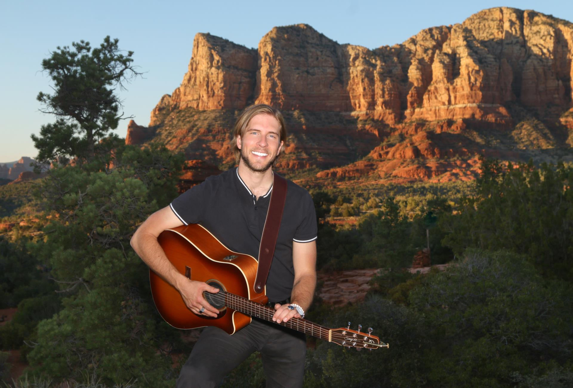 Dan with guitar red rock background
