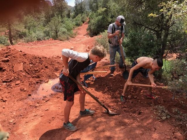 Kids digging in the dirt helping build the trails